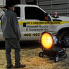 A young man warms himself near a MI-T-M infra red heater during KNID Agrifest 2013 Friday at the Chisholm Trail Expo Center. (Staff Photo by BONNIE VCULEK)