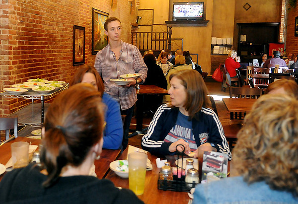 A waiter serves salads to several clients during lunch at the new Napoli's location at 223 S. Grand Friday. (Staff Photo by BONNIE VCULEK)