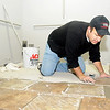 Dan King installs restroom tiles at the new Junior Welfare League Return Engagement location on N. Grand Saturday. The organization's official move is slated for Jan. 19-20. (Staff Photo by BONNIE VCULEK)