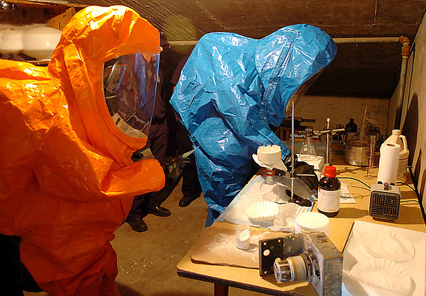 Oklahoma National Guardsman, Staff Sgt. Daniel Pierce and Sgt. Ronald Poland, of the 63rd Weapons of Mass Destruction Civil Support Team, catalog items of a meth lab during a joint exercise with the Enid Fire Department at the Garfield County Fairgrounds. (Staff Photo by BILLY HEFTON)