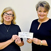 Gayle Wynne (right) accepts a check from Becky Allen for the charity Food 4 Kids.