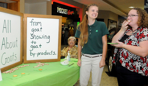 Frontier 4-H's Jaclyn McCormick (center) laughs as Cindy Burgess, from Ponca City, tries a vegetable mix goat cheese Saturday during the Garfield County 4-H Day at Oakwood Mall. (Staff Photo by BONNIE VCULEK)