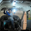 Paul Wilson glues a new headliner into a Cessna Caravan 208-B at Aircraft Structures International Corporation Thursday, Jan. 24, 2013, at Enid Woodring Regional Airport. Wilson has been employed for 5 1/2 years for the Enid business. (Staff Photo by BONNIE VCULEK)
