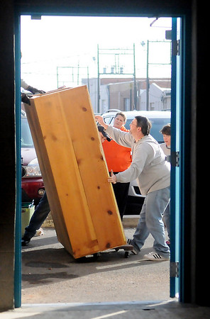 Junior Welfare League members, spouses, and friends unload heavy cabinets from an Atwood's semi-truck as they move their Return Engagement business into the new Grand Avenue location Saturday, Jan. 26, 2013. (Staff Photo by BONNIE VCULEK)