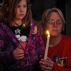 Lacie Williams and Amanda Kendall (from left) hold hands as they pause to remember Heath Crites during a candlelight vigil at Meadowlake Park North Tuesday, Jan 22, 2013. The Enid Police Department continues their investigation of Crites' murder at his home Dec. 22, 2012. (Staff Photo by BONNIE VCULEK)