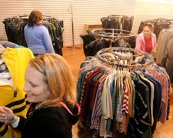 Amy Ratzlaff (lower left), Lori McMillin (top, left) and Brenda Rogers (right) arrange donated clothing inside Junior Welfare League's Return Engagement as the organization moves to Grand Avenue Saturday, Jan. 26, 2013. (Staff Photo by BONNIE VCULEK)