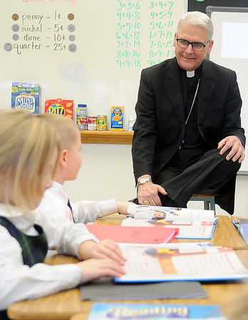 Archbishop Paul Coakley visits with first grade students at St. Joseph Catholic School before the 10 a.m. Mass at St. Francis Xavier Catholic Church Wednesday, Jan. 22, 2014. The Archbishop briefly discussed his recent trip to Bethlehem, asked the students what they had been learning, and answered their questions during an informal visit in each classroom. (Staff Photo by BONNIE VCULEK)