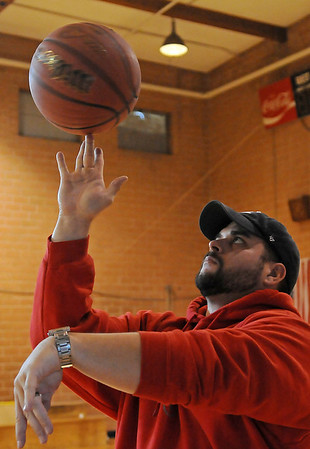 Blake Gibson, a member of the Knights of Columbus, spins a basketball on his fingertips as he assists with the organization's free throw championships in the St. Joseph Catholic School gym Saturday, Jan 11, 2014. (Staff Photo by BONNIE VCULEK)