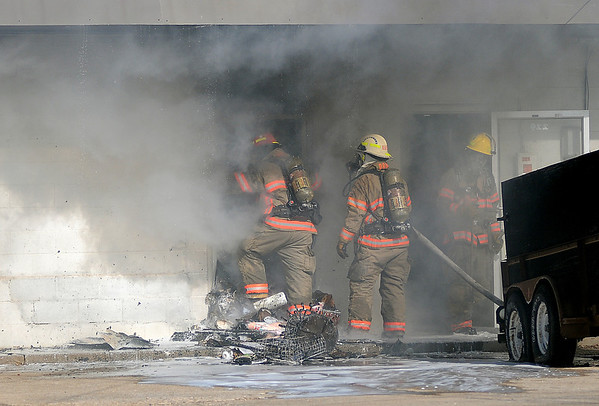 Smoke rolls from a building as Capt. Denton Morgan and Lt. Shawn Kuehn, with the Enid Fire Department, enter a rear entrance as firefighters battle a blaze in the 200 block of West Cherokee Friday, Jan. 17, 2014. (Staff Photo by BONNIE VCULEK)