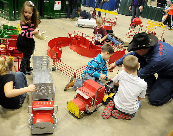 Jerry Sims (right), the Happy Toy Maker, plays with the children who love his toys during the 18th annual KNID Agrifest at the Chisholm Trail Expo Center Saturday, Jan. 11, 2014. (Staff Photo by BONNIE VCULEK)