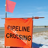 Pipeline Crossing warning signs appears along U.S. 81 near the Waukomis Booster Station two and one-half miles south of Enid as crews prepare new lines for installation Tuesday, Jan. 07, 2014. (Staff Photo by BONNIE VCULEK)