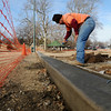 Rosendo Lemon removes wooden forms from the new concrete stem wall around the expanded playground area at Government Springs Park Wednesday, Jan. 15, 2014. The City of Enid is currently updating playgrounds at Glenwood, Government Springs and Meadowlake Parks. (Staff Photo by BONNIE VCULEK)