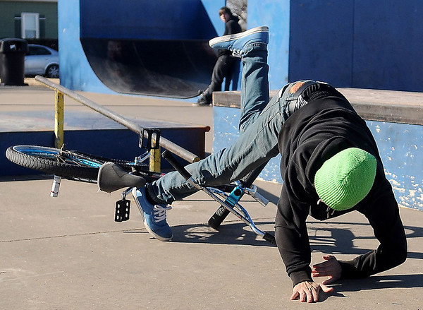 Thomas Martens tumbles over his handlebars as he tries an over tooth move at the City of Enid skate park Monday, Jan. 20, 2014. Martens landed perfectly on his second try. (Staff Photo by BONNIE VCULEK)
