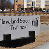 A jogger passes the Cleveland Street Trailhead sign Tuesday afternoon. The National Weather Service is forecasting high temperatures in the mid-40's today and the low 20's Thursday. (Staff Photo by BILLY HEFTON)