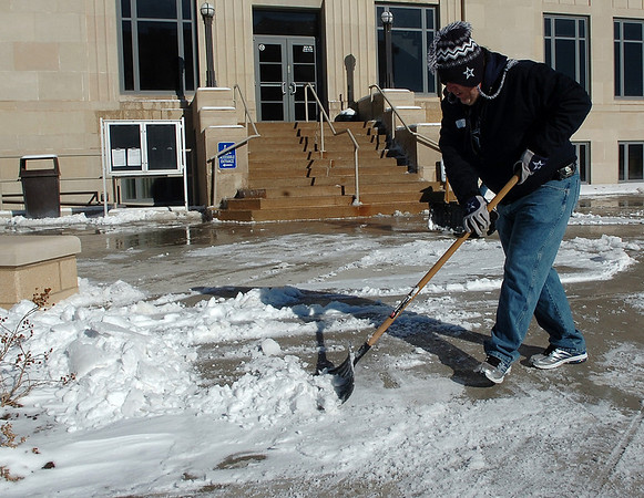Paul McKittrick shovels snow from the entrance of the Garfield County Courthouse Sunday. (Staff Photo by BILLY HEFTON)