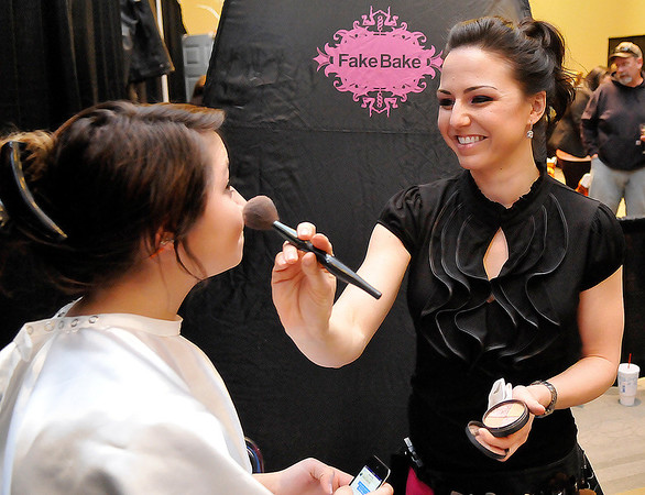 Christian Teal gets make-up applied from Summer Glitsch at the Heartquest Salon booth Sunday during the Weddings with Elegance bridal show inside Convention Hall. (Staff Photo by BILLY HEFTON)