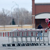 A stockman is dressed for the cold temperatures as he gathers shopping carts from the Jumbo's East parking lot Monday. (Staff Photo by BILLY HEFTON)