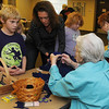 Norma Barton (bottom center) teaches Lance Frantz how to sew a pair of felt mittens during the Cherokee Strip Regional Heritage Center family Saturday activities Jan. 18, 2014. (Staff Photo by BONNIE VCULEK)