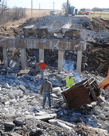 Workers salvage metal from the old Bruce Perry Memorial Bridge after the Oklahoma Department of Transportation closed OK 132, 4 miles north of Drummond, as crews demolish the bridge over Turkey Creek Wednesday, Jan. 15, 2014. Completion of the new bridge is slated for May 2014. Individuals living in the area have access to other county roads during construction. (Staff Photo by BONNIE VCULEK)
