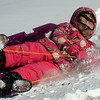 A sledder takes a tumble at the bottom of the north Van Buren overpass embankment Sunday. (Staff Photo by BILLY HEFTON)