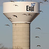 Canada geese fly past an Enid water tower as they prepare for a landing at Meadowlake Park Wednesday, Jan. 8, 2014. (Staff Photo by BONNIE VCULEK)