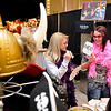 Shay Weder and Kimber Jackson pick their costumes at the Mug Shots booth Sunday during the Weddings with Elegance bridal show inside Convention Hall. (Staff Photo by BILLY HEFTON)