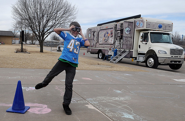 A fifth-grade student holds optical illusion glasses over his eyes as he tries to kick a blue cone during science matters activities outside the Oklahoma Museum Network science bus at Coolidge Elementary School Tuesday, Jan. 14, 2014. (Staff Photo by BONNIE VCULEK)