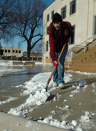 Lori Stanley shovels snow from the entrance of the Garfield County Courthouse Sunday. (Staff Photo by BILLY HEFTON)