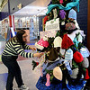 Leslee Ballard, an associate at the Public Library of Enid and Garfield County, places a crocheted scarf on the Christmas tree at the library Thursday, Jan. 02, 2014. The new mittens, hats and scarves will be distributed to area children. (Staff Photo by BONNIE VCULEK)