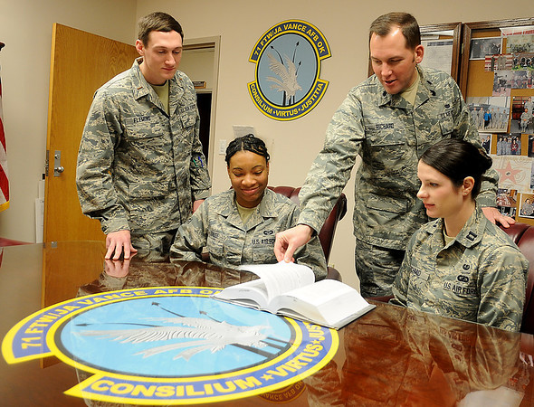 Lt. Col. Theodore Richard (standing right), the Staff Judge Advocate at Vance Air Force Base, works with his staff (from left) Lt. Logan Fleming, Airman Shafiyquca Gause and Capt. Megan Schmid Wednesday, Jan. 22, 2014. (Staff Photo by BONNIE VCULEK)