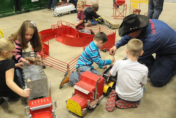 The Happy Toy Maker, Jerry Sims (right), kneels as he shows Creed and Cole Watkins how to disconnect a toy trailer. Sims, a Diamond Corrals dealer, creates the custom-made, indestructible toys for children and takes them to several trade shows each year. (Staff Photo by BONNIE VCULEK)