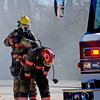 An Enid firefighter removes an empty oxygen tank from a Captain's back after the two battled a blaze in the 200 block of West Broadway Friday, Jan. 17, 2014. (Staff Photo by BONNIE VCULEK)