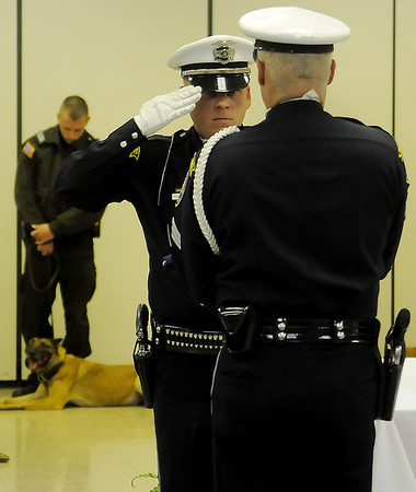 Enid Police Department Officer Kelly Smith salutes Sgt. Quent Tubbs during the K-9 Rex Memorial Service flag presentation at 116 W. Oxford Friday, Jan. 03, 2014. K-9 Rex and Enid Police Officer Ryan Fuxa worked as a dual purpose K-9 team over eight years until K-9 Rex retired in October 2010. Upon retirement, K-9 Rex lived with Officer Fuxa and his family until his death Dec. 14, 2013. (Staff Photo by BONNIE VCULEK)