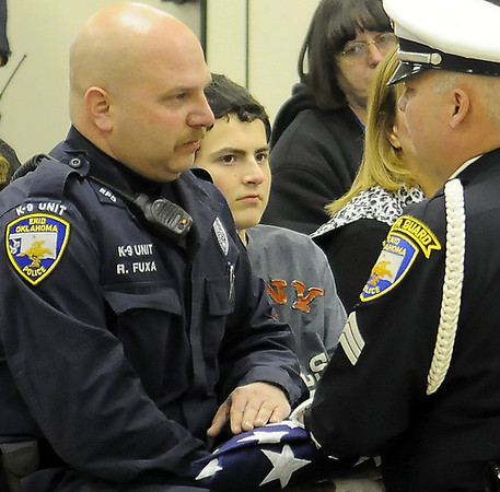 Tucker Fuxa (center) listens, as his father, Enid Police Officer Ryan Fuxa, (left) receives a United States flag from fellow officer, Sgt. Quent Tubbs, during the K-9 Rex Memorial Service at 116 W. Oxford Friday, Jan. 03, 2014. Officer Ryan Fuxa and K-9 Rex worked as a dual purpose K-9 team for over eight years until K-9 Rex's retirement in Oct. 2010. K-9 Rex spent the remaining years of his life with his partner Officer Ryan Fuxa and his family. (Staff Photo by BONNIE VCULEK)