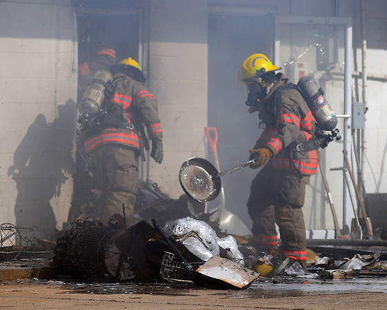 Enid firefighters remove debris from a building as they battle a blaze in the 200 block of West Cherokee. The Enid Fire Department, Enid Police Department and Life EMS responded to the scene. (Staff Photo by BONNIE VCULEK)