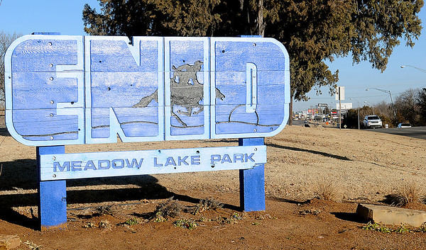 A new Enid Meadow Lake Park sign glistens in the sun as traffic moves along S. Van Buren Friday, Jan. 03, 2013. City of Enid Park and Recreation Department employees installed the re-painted signs as part of the Branding Enid project. (Staff Photo by BONNIE VCULEK)