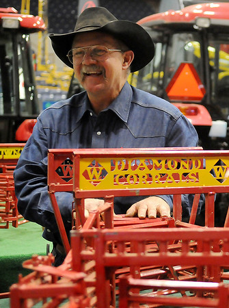 Jerry Sims, The Happy Toy Maker, pauses near miniature Diamond Corrals that he made in his toy factory in Happy, Texas, during the 18th annual KNID Agrifest at the Chisholm Trail Expo Center. Sims, a Diamond Corrals dealer and creator of indestructible toys for children, takes his toy trucks, trailers, corrals, and animals to several trade shows throughout the year. (Staff Photo by BONNIE VCULEK)