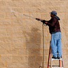The sun casts a man's shadow as he washes the exterior of CVS Pharmacy Tuesday, Jan. 14, 2014. (Staff Photo by BONNIE VCULEK)