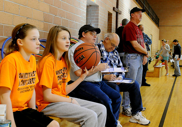 Zoey Reherman and Gabby Bartley (from left) will shoot hoops during the Knights of Columbus free throw championship as judges, Brian Campbell and Roland Boudreau (center) keep score in the St. Joseph Catholic School gym Saturday, Jan. 11, 2014. (Staff Photo by BONNIE VCULEK)