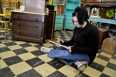 Jamie Davis paints a sign inside Lola's Boutique Wednesday. (Staff Photo by BILLY HEFTON)