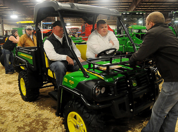 Roy Johnston and Ryan Johnson, with P & K Equipment, discuss the benefits of owning a John Deere 825i Gator during the 18th annual KNID Agrifest at the Chisholm Trail Expo Center Friday, Jan. 10, 2014. (Staff Photo by BONNIE VCULEK)