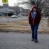 Enid High School appears in the background (center) as Daniel Gutierrez curls his fingers inside the sleeves of his light-weight, hooded jacket during his walk home from Emerson Middle School Thursday, Jan. 23, 2014. Gutierrez, like many other students who attend Enid Public Schools walks to and from school even when temperatures and wind chills are below zero. (Staff Photo by BONNIE VCULEK)