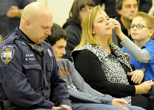 Wyatt Fuxa (right) gently wipes a tear from his mother's eye as Enid Police Officer Ryan Fuxa (left), his wife Marla, and their sons, Tucker and Wyatt, mourn the loss of K-9 Rex during a special memorial service Friday, Jan. 03, 2014. Enid Police Officer Ryan Fuxa and K-9 Rex were a dual purpose K-9 team from April 2002-October 2010. Upon retirement, K-9 Rex lived with Officer Ryan Fuxa and his family until his death Dec. 14, 2013. (Staff Photo by BONNIE VCULEK)