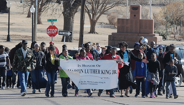 Marchers honor the memory of Dr. Martin Luther King, Jr. during a holiday commission commemorative march from Grayson Missionary Baptist Church, 334 E. Garriott, past the Cherokee Strip Regional Heritage Center, along Owen K. Garriott to 7th Street and west on E. Oklahoma as they circle Government Springs Park Saturday, Jan. 19, 2014. The MLK Celebration continues Sunday at the Central Assembly of God Family Life Center at 4 p.m. (Staff Photo by BONNIE VCULEK)