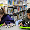 Talynn Burton and Don Romo (from left) play games on the new Samsung tablets at the Public Library of Enid and Garfield County Thursday, Jan. 2, 2014. The Library's newest technology is available for use in the children and teen section. (Staff Photo by BONNIE VCULEK)
