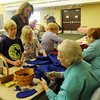 Norma Barton (lower left) shows children how to cut out a pair of felt mittens during the Cherokee Strip Regional Heritage Center family Saturday activities Jan. 18, 2014. (Staff Photo by BONNIE VCULEK)