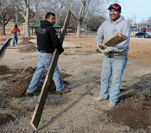 Rosendo Lemon, Jose Acosta and Ramon Castorena (from left) remove wooden forms from the new concrete stem wall around the Government Springs Park enlarged playground area Wednesday, Jan. 15, 2014. The City of Enid is currently updating children's playgrounds at Glenwood, Government Springs and Meadowlake Parks. (Staff Photo by BONNIE VCULEK)
