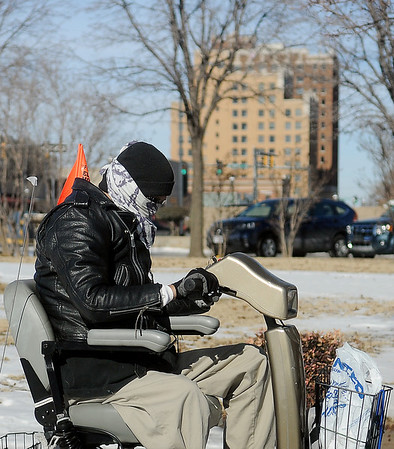 A man protects himself from the cold as he rides his mobile wheel chair along the sidewalk in front of the Public Library of Enid and Garfield County Tuesday, Jan. 07, 2014. After record lows reached single digits again Monday night, temperatures rose into the low 40s by mid-afternoon. (Staff Photo by BONNIE VCULEK)