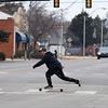 A longboarder crosses Broadway in downtown Enid Saturday January 14, 2014. (Billy Hefton / Enid News & Eagle)