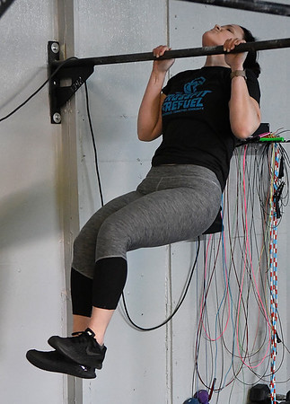 Elizabeth Dickson does a pull-up during a class at CrossFit ReFuel January 17, 2017. (Billy Hefton / Enid News & Eagle)